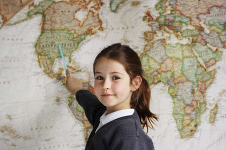 human geography: A school girl indicating the United States of America on a world map
