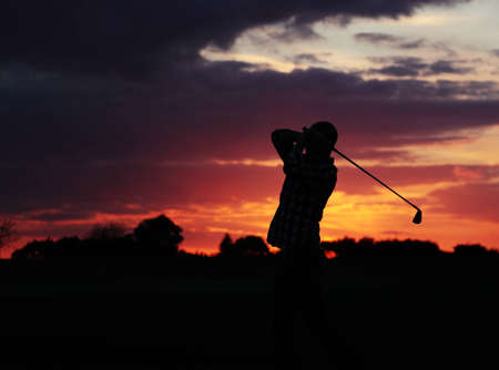 A golfer making the most of the remaining light and playing on
