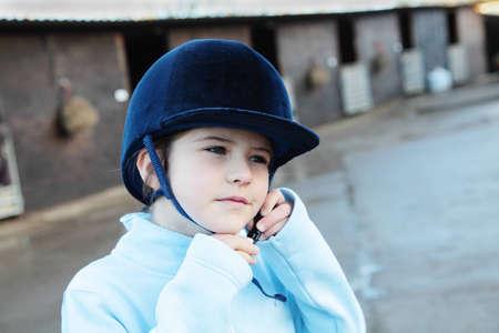 riding helmet: Una ni�a en un casco de equitaci�n de establos