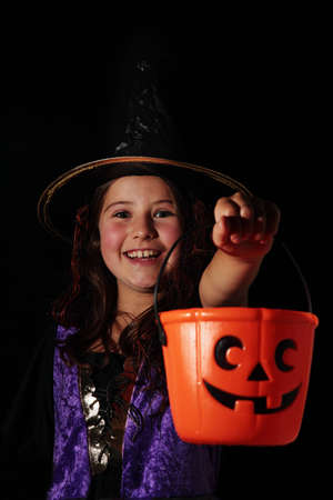 A cute Halloween witch enjoying trick or treat Stock Photo - 8868436