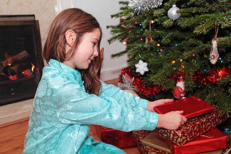log fire: Una ragazza di Natale di apertura presenta sotto un albero di Natale con un caminetto in background