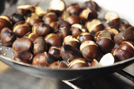 chestnut: Chestnuts being roasted in a special pan with holes