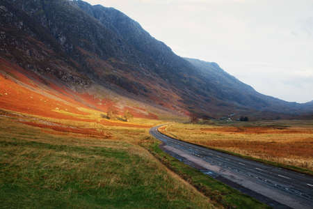 A road disappearing into the distance through the Highlands of Scotland as the sun sets