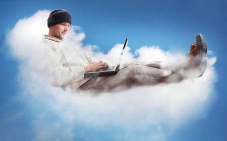Un hombre en una nube de funcionamiento de un ordenador portátil. El hombre está vestido de manera informal para representar a la mayoría de los trabajadores de TI. El concepto es el Cloud Computing - software / informática en la nube. Foto de archivo