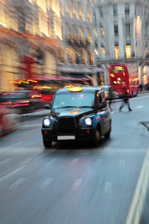 A london taxi with other taxis and a typical London bus in the background.  The image deliberately has lots of zoom blur. photo