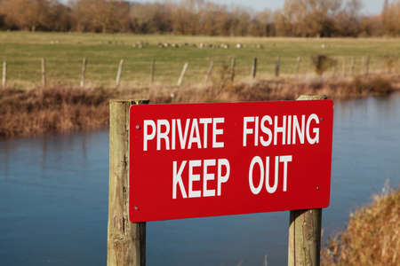 keep out: A Private Fishing sign next to a river