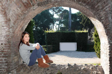 A happy girl sitting in an archway