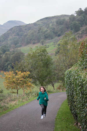 A young girl running up a road in beautiful surroundings