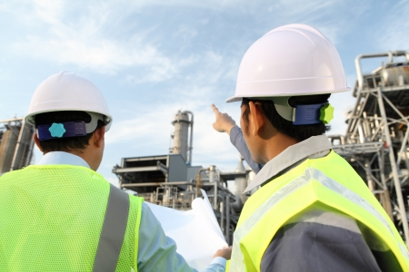 refinery: two engineer discussion about plan working on location site