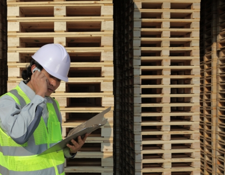 warehouse worker calling beside stacking pallet  photo