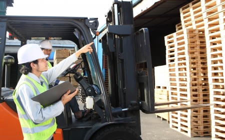 warehouse worker calling beside stacking pallet