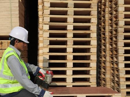 pallet: worker using nail gun to nail top of pallet