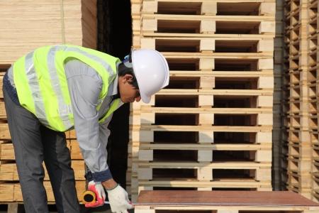 Worker carpenter measures the pallet  photo