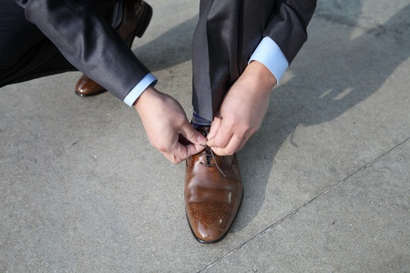A businessman tying his shoelaces photo