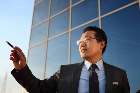 copyspace corporate: businessman pointing with pen front the office smile