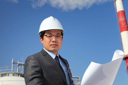 industrial engineer checking plan on location site with tower and blue sky background photo