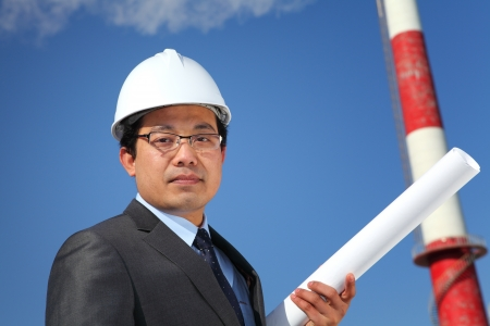 businees: industrial engineer checking plan on location site with tower and blue sky background Stock Photo