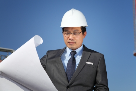 businees: industrial engineer checking plan on location site with clean sky background
