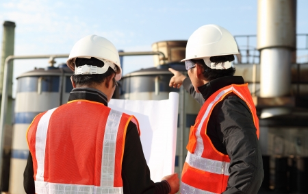 two engineer oil industry discussing a new project with large oil refinery background  Stock Photo