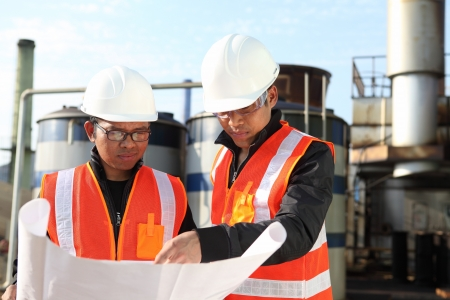 gas plant:  two engineer checking a drawing