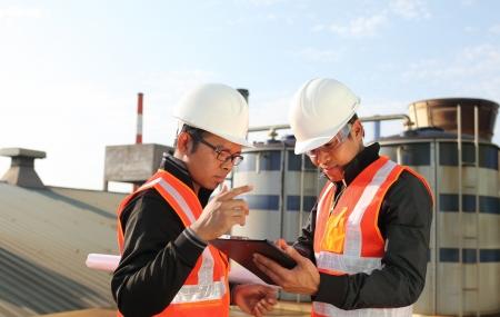 refinería de petróleo: dos industria petrolera ingeniero discutiendo un nuevo proyecto con el fondo grande refinería de petróleo Foto de archivo