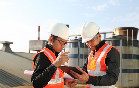 refineries: two engineer oil industry discussing a new project with large oil refinery background  Stock Photo