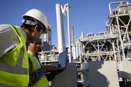 refiner�a de petr�leo: dos ingenieros de potencia y energ�a en el sitio discusi�n ubicaci�n Foto de archivo