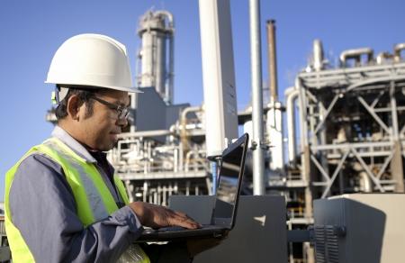 ingenieria industrial: ingeniero de potencia y energ�a usando la computadora port�til en el sitio ubicaci�n Foto de archivo