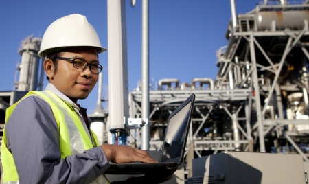 oil and gas industry: engineer power and energy using laptop on location site