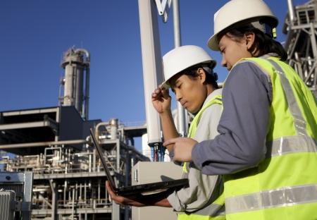 refinería de petróleo: dos ingenieros de potencia y energía en el sitio discusión ubicación utilizando equipo portátil