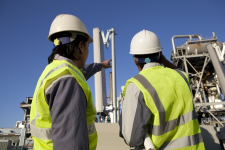 plant oil: two engineer power and energy discussion on location site Stock Photo