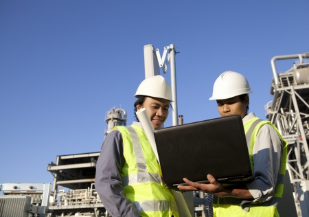tehnology: two engineer power and energy discussion on location site using laptop