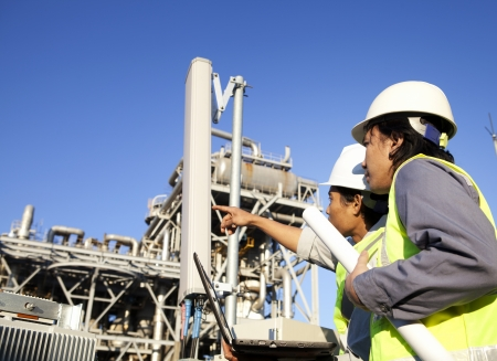 oil and gas: two engineer power and energy discussion on location site Stock Photo