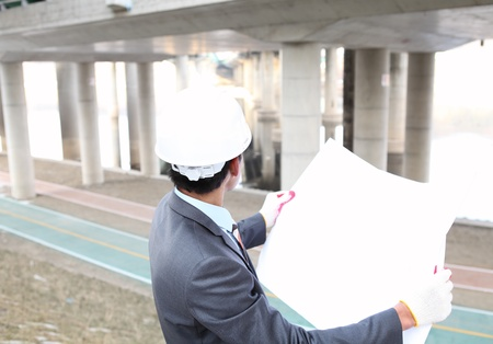 architect  with blueprint on highway construction site photo