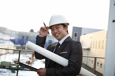 supervisión: joven arquitecto con el modelo blanco celebración casco y el portapapeles sonriente mirando a la cámara