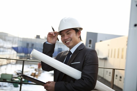 supervision: young architect with white helmet holding blueprint and clipboard smiling look at the camera