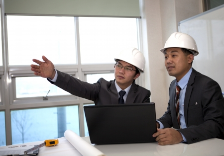 hardworking: architects sitting at table and discussing a project in the office Stock Photo
