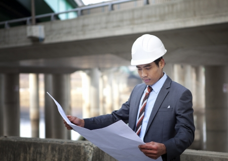 young architect with blueprint on highway construction site  photo
