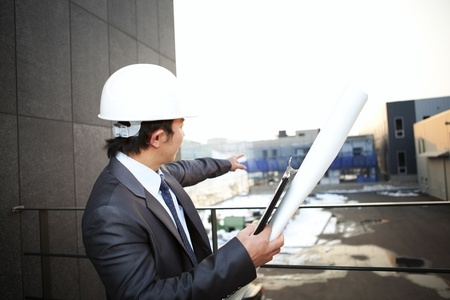 young architect with white helmet holding blueprint and clipboard pointing at the buiding construction photo