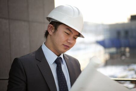 close-up young asia architect with white helmet  looking blueprint serious photo