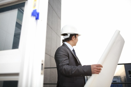 young architect with white helmet holding blueprint checking plan standing front office building photo