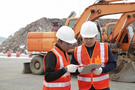 deux discussion travailleur de la construction sur le site de construction avec pelle sur le fond