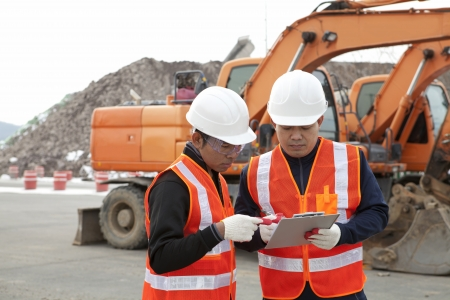 two construction worker discussion on construction site with excavator on the background Stock Photo