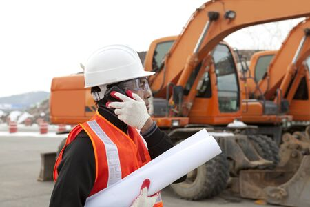 road construction worker holding blueprints and talking on the phone Stock Photo - 17345851