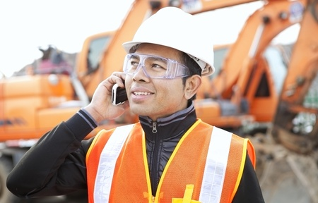 road construction worker using mobilephone standing in front of excavator Stock Photo - 17345861