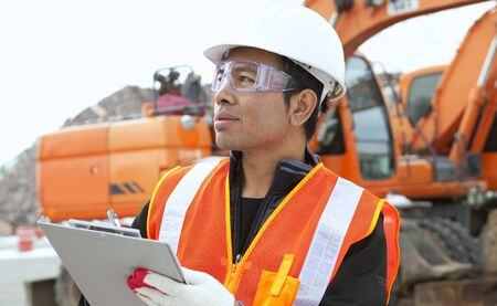 portrait construction worker in front of excavator checking plan Stock Photo - 17366348