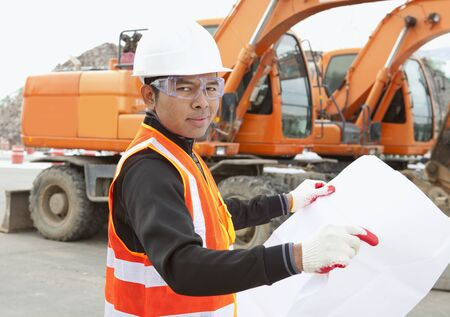 heavy equipment operator: road construction worker and heavy equipment on the background Stock Photo
