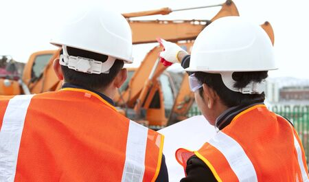 two construction worker discussion on construction site with excavator on the background Stock Photo - 17232079