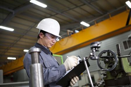 obrero: escrito técnico mecánico en bloc de notas en la fábrica