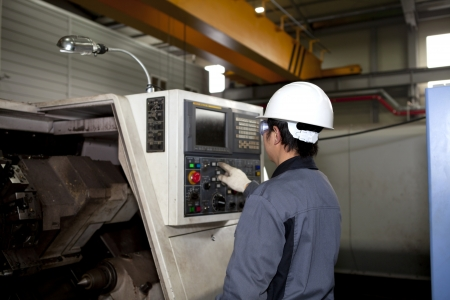 man machine: technician worker operating cnc machine center Stock Photo
